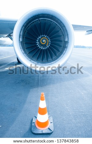 Jet engine with traffic cone in front, blue light - stock photo
