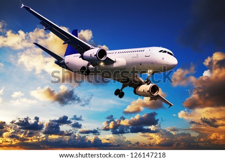 Jet in a sky at sunrise time - stock photo