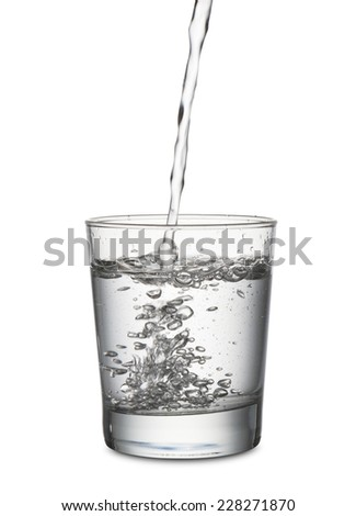 jet of water that fills a glass, on white background - stock photo