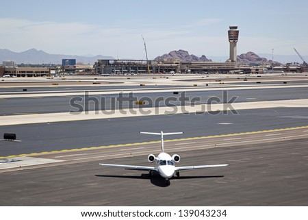 Jet on tarmac with airport tower and terminal backdrop - stock photo