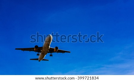 Jet plane flying in blue sky, preparing for landing.