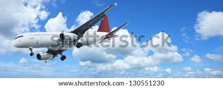 Jet plane in a blue sky. Panoramic composition. - stock photo