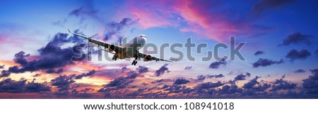 Jet plane is maneuvering for landing in a spectacular sunset sky. Panoramic composition. - stock photo