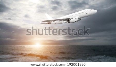 Jet plane over the sea at sunset time - stock photo