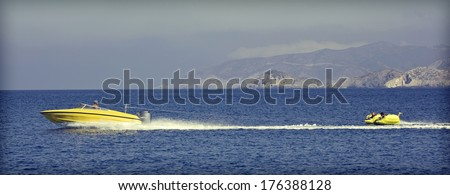 Jet ski and two kids trying not to fall off a water tube  - stock photo