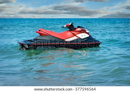 Jet-ski on waves of the sea against the blue sky - stock photo