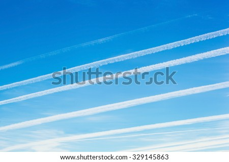 Jet trails, known as chemtrails over blue sky