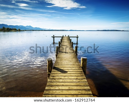 Jetty at the Chiemsee in Germany with blue sky - stock photo