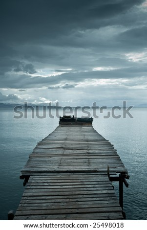 Jetty before storm dramatic clouds - stock photo