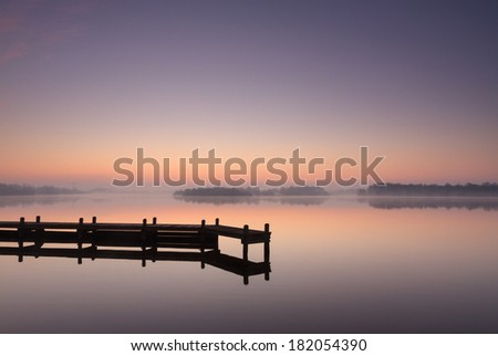 Jetty during a tranquil, foggy dawn at a lake. - stock photo