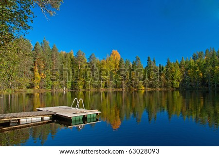 Jetty from sauna to lake with beutiful colors on autumn and reflection of trees in Finland. - stock photo
