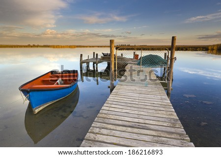 Jetty leading into river and fishing boat at sunset