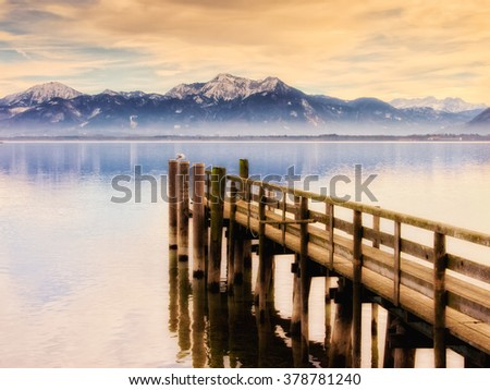 jetty on lake chiemsee with mountains in background - stock photo