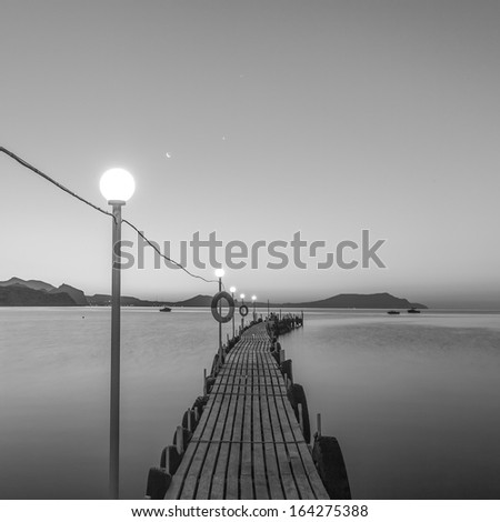 Jetty on sea at dawn. Black and white. - stock photo