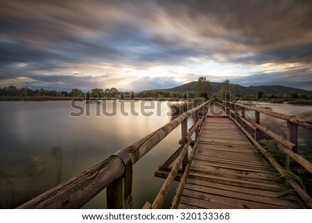 jetty on the lake at sunset - stock photo