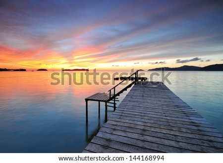 Jetty pointing toward the ocean with dramatic sunset - stock photo