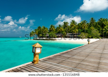 jetty to a tropical beach - stock photo