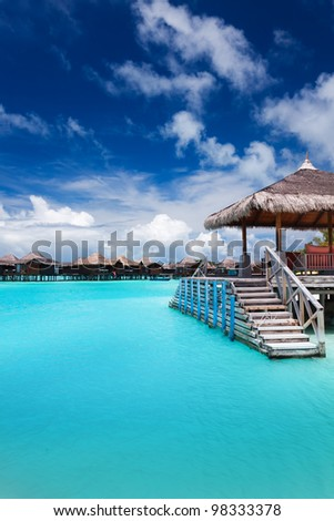 Jetty with steps into amazing tropical blue lagoon - stock photo