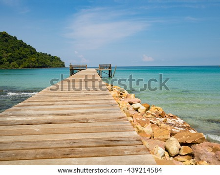 Jetty wooden bridge into blue sea and sky. Pier over water. Vacation And tourism concept. Tropical resort. Jetty on Koh Kood Island, Thailand.
