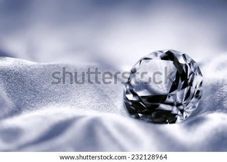 Jewel on satin fabric background - stock photo