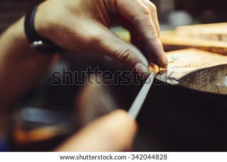 Jeweler crafting jewelry on his workbench - stock photo