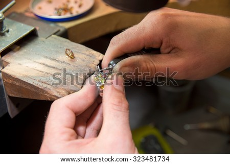 jeweler fixes gems on gold product - stock photo