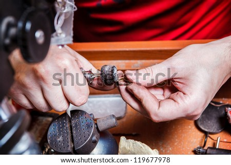 Jeweler polishes golden earring with a polishing wheel - stock photo
