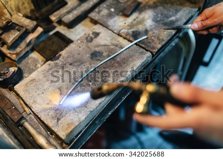 Jeweler processing metal by heating it up to proper temperature - stock photo