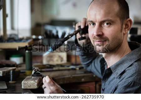 Jeweler silver soldering in his workshop looking at the camera. - stock photo