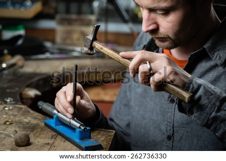 Jeweler working with the hammer on wedding gold ring in his workshop. Craft jewelery making.