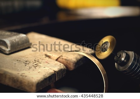 Jeweller working with bracelet by polishing motors tool. Jewelry workplace. Toned image