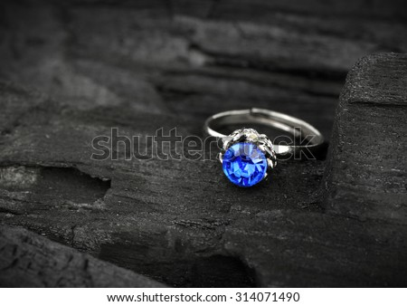 jewellery ring witht blue sapphir on dark coal background, soft focus - stock photo