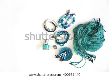 Jewelry, decorations of blue and turquoise. White background. Bracelets, nail polish, earrings and necklaces. - stock photo
