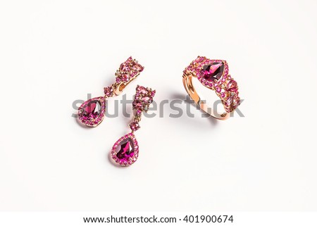 Jewelry gold set of ring and earrings with pink topaz on white background - stock photo