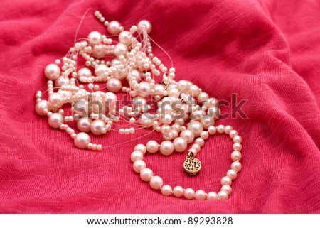 Jewelry made of pearls on the pink background