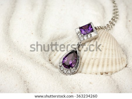 jewelry pendant with gems and diamonds on sand background