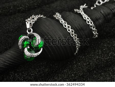 jewelry pendant with gems on black background - stock photo
