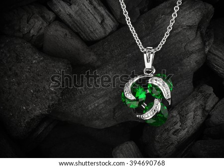 jewelry pendant witht gem on dark coal background, copyspace