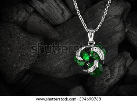 jewelry pendant witht gem on dark coal background, copyspace - stock photo