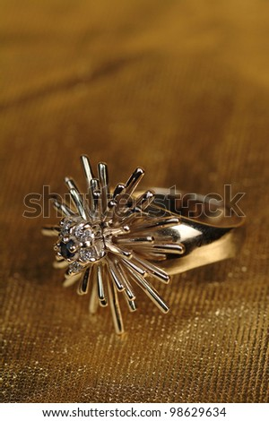 jewelry ring in the shape of a flower with a red stone on a black background - stock photo