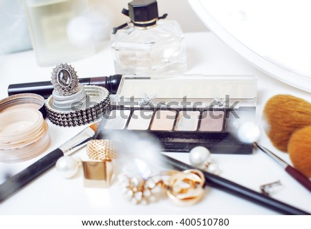 Jewelry table with lot of girl stuff on it, little mess in cosmetic brushes, interior concept - stock photo