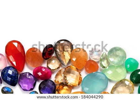 Jewels collection on the white background. All real gemstones: carnellian, amethyst brazilian, rainbow and peach moonstone, citrine, sapphire, lapis lazuli, rose quartz, chrysophase, ruby and more. - stock photo