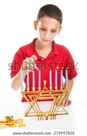 Jewish boy using the shamash candle to light the menorah for Hanukkah.   - stock photo