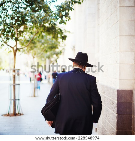 Jewish business man in the street with briefcase in his hand. Man turned his back. - stock photo