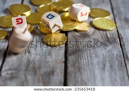 Jewish holiday hannukah symbols - chocolate coins and wooden dreidels. Copy space background. - stock photo