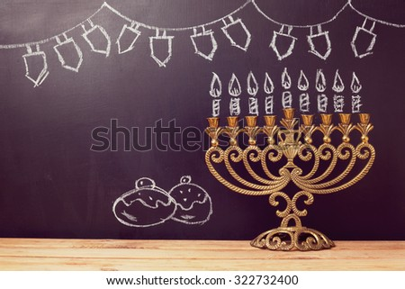 Jewish holiday Hanukkah background with menorah over chalkboard with hand sketched symbols - stock photo