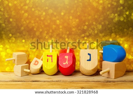 "Jewish holiday Hanukkah background with spinning top dreidel on wooden table over golden bokeh. The Hebrew letters are the first letters of the words which means ""A great miracle happened here."" - stock photo"
