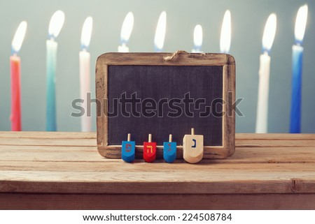 Jewish Holiday Hanukkah background with wooden dreidel spinning top and chalkboard over candles - stock photo