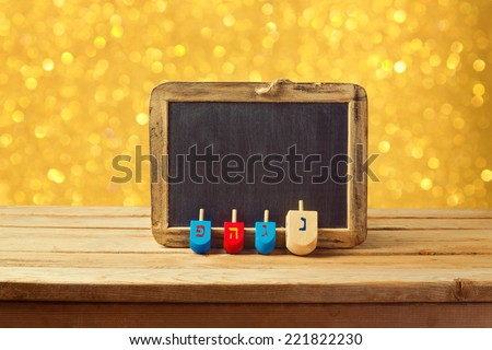Jewish Holiday Hanukkah background with wooden dreidel spinning top and chalkboard over golden bokeh lights - stock photo