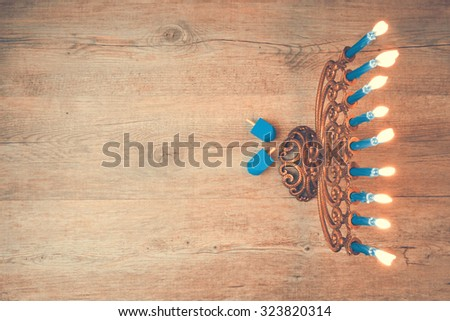 Jewish holiday Hanukkah creative background with menorah. View from above with focus on menorah. Retro filter effect. - stock photo